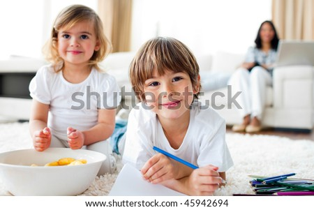 Smiling siblings eating chips and drawing lying on the floor