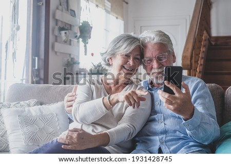 Smiling sincere mature older married family couple holding mobile video call conversation with friends, enjoying distant communication with grown children, using smartphone applications at home. Stock photo ©