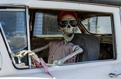 Smiling Skeleton in Sunglasses and a Red Baseball Cap Driving a Car
