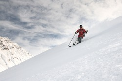 Smiling skiier in red jacket slides down the snowy mountain side