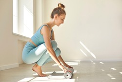 Smiling slender gymnast woman in blue sports suit rolling her gray yoga mat on the wooden floor by the window. Woman trains in a spacious and bright gym. Healthy life and yoga concept.
