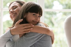 Smiling small preschooler girl look at camera hugging make peace reconcile with loving young mom, happy little daughter embrace cuddle mother share enjoy tender close moment at home together