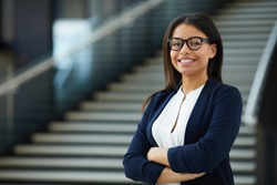 Smiling smart attractive young black lady in glasses standing in lobby and looking at camera, she working in prosperous company