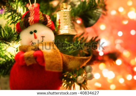 Smiling snow man Christmas tree decoration hanging on the spruce - stock photo