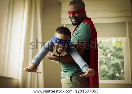 Smiling son and father pretending to be a superhero at home