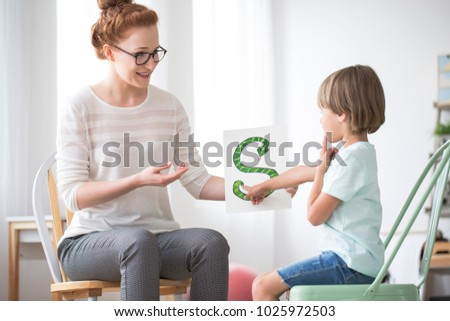 Smiling speech teacher teaching a boy pronunciation by showing him a snake picture