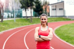 Smiling sports woman standing with arms folded