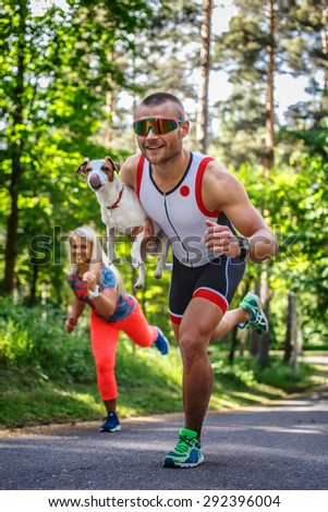 Smiling sportsman in sunglasses on the run with small dog in his hand. Running woman on background.