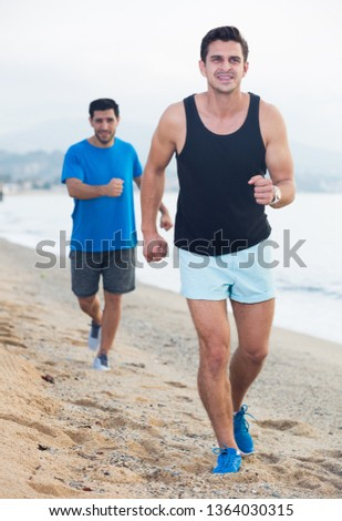 Smiling sportsmen are joggning in time warm-up on the beach.