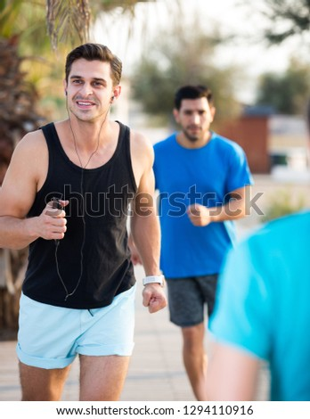 Smiling sportsmen are joggning race in time warm-up in the park near beach.