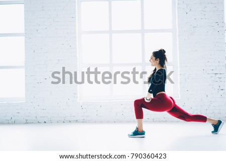 Smiling sportswoman enjoying workout in white interior gym squatting training lower body and legs muscles,active brunette girl motivated with fitness goals keeping perfect body shape doing exercises #790360423