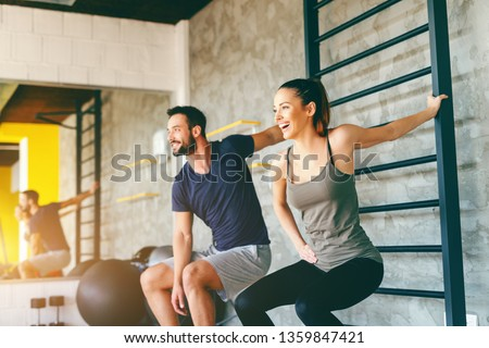 Smiling sporty couple stretching arms in squatting position. Gym interior.