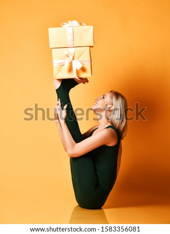 Smiling sporty girl does yoga asana stretching exercise holds New Year Christmas gifts boxes presents on her upturned legs feet. Healthy life fitness concept on yellow background
