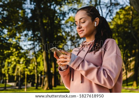 Smiling sporty girl is using her phone with earbuds walking in a park Stock photo ©
