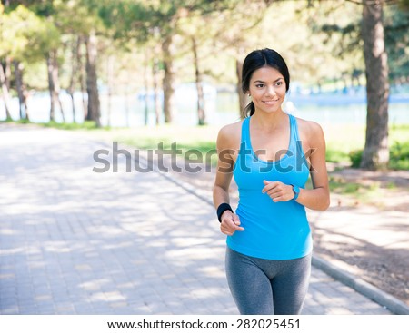smiling sporty woman running...