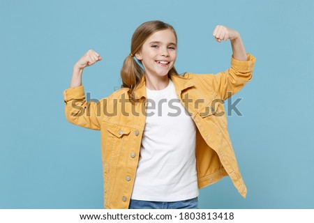 Smiling strong little blonde kid girl 12-13 years old in yellow jacket showing biceps, muscles isolated on blue background children studio portrait. Childhood lifestyle concept. Mock up copy space. Stock photo ©