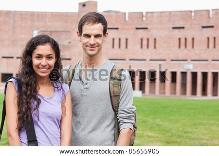 Smiling student couple posing outside a building