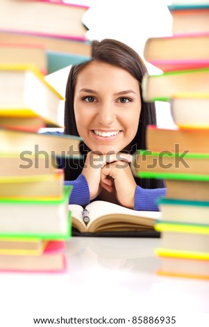 smiling student girl between stack of books, isolated on white background