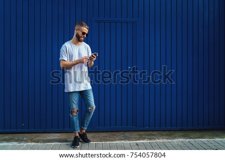 Smiling student guy chatting online  via social network on a mobile phone while walking the street. Stylish hipster male checking email box on a smartphone while standing on a blue wall background.