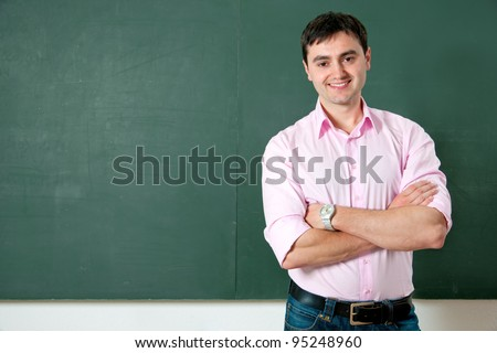 smiling student or teacher at the blackboard
