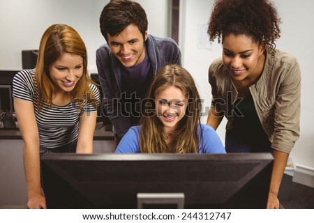 Smiling students sitting at desk using computer together in classroom ストックフォト ©