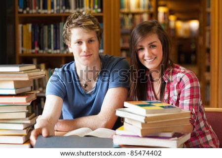 Smiling students surrounded by books in a library