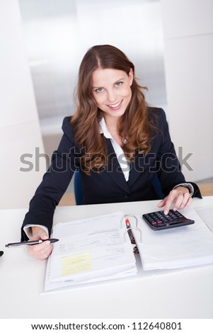 Smiling stylish businesswoman sitting at her desk using a calculator and completing an analysis sheet or journal
