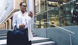 Smiling stylish content black female in earphones with briefcase surfing smartphone joyfully while walking downstairs beside office centre in city