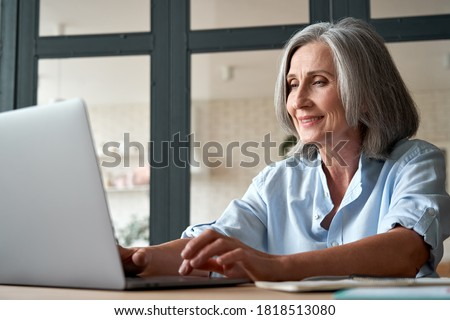 Smiling stylish mature middle aged business woman using laptop computer sitting at workplace desk. Happy senior older lady, 60s grey-haired businesswoman working typing on pc at home or from office.