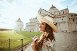 smiling stylish solo tourist woman in floral dress with vintage camera and hat near Pisa Cathedral.