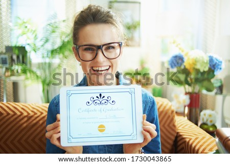 smiling stylish woman in jeans shirt in the modern house in sunny day showing electronic Certificate of Graduation on tablet PC screen.