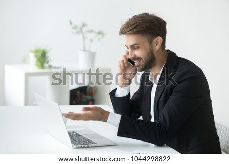Smiling successful businessman in suit talking on phone using laptop sitting at office workplace, young entrepreneur making answering call consulting client speaking by cell, holding mobile interview