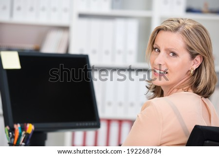 Smiling successful businesswoman sitting at her desk in the office in front of a desktop monitor turning to give the camera a happy smile
