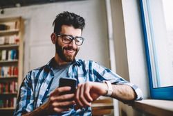 Smiling successful hipster guy in eyewear checking time on wearable smartwatch while waiting for meeting at university campus, happy man holding mobile phone in hand and reading message on wristwatch