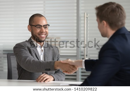 Smiling successful male african american job applicant shake hand of hr employer get hired employed at interview, happy mixed race bank manager broker handshake client customer at business meeting