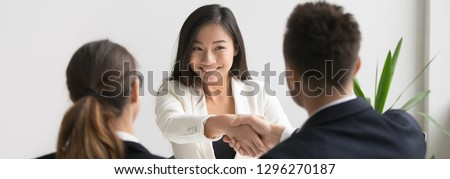 Smiling successful young asian applicant handshake with hr manager feels happy getting hired, boss congratulating employee new job employment concept. Horizontal photo banner for website header design