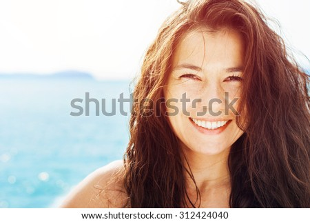 Smiling Suntanned Woman On the Background by Blue Sea in Sunlight. Summer day