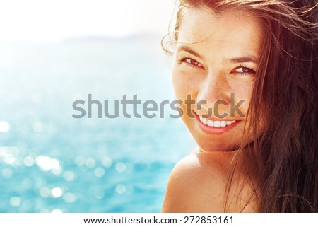 Stock Photo Smiling Suntanned Woman On the Background from Blue Sea in Sunlight. Summer day