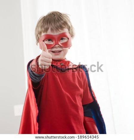 Smiling super hero kid at home with thumb up, looking at camera.