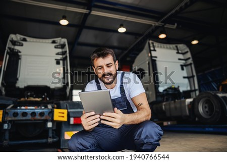 Smiling tattooed bearded blue collar worker in overalls using tablet to check on delivery while crouching in garage of import and export firm. In background are trucks. Stock foto ©