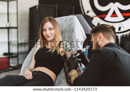 Smiling tattooed girl looking in camera while professional tattooer doing tattoo on hand using tattoo machine in studio