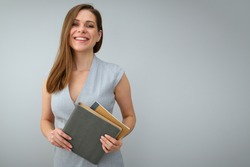 Smiling teacher holding books and standing near to copy space. Isolated female portrait.