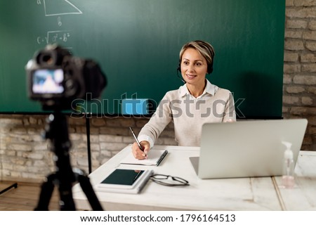 Smiling teacher holding online lecture from the classroom during COVID-19 lockdown. Stock photo ©