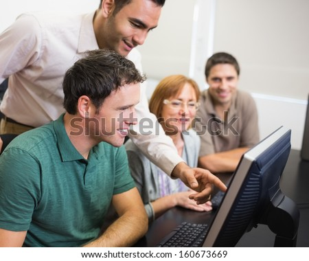 Smiling teacher showing something on screen to mature student in the computer room