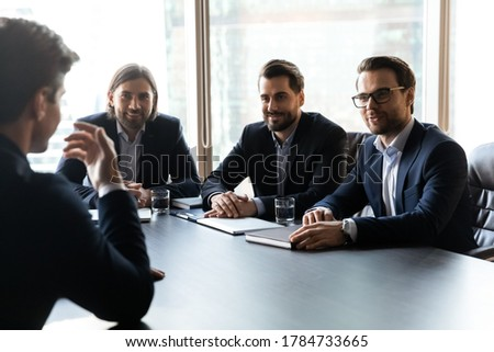 Smiling team of professional recruiters in formal suits sitting at table in front of young male job seeker, involved in hiring process, satisfied with working experience of skilled applicant.