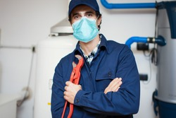 Smiling technician repairing an hot-water heater wearing a mask, coronavirus concept