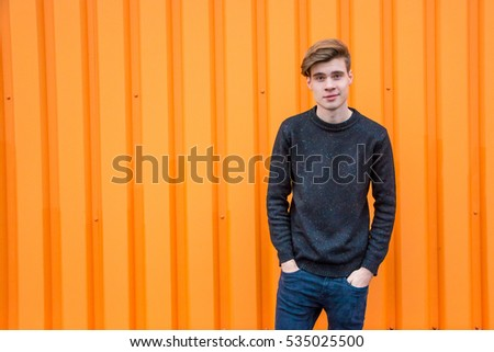 Smiling teen boy in black over contrasting orange background portrait with copyspace #535025500