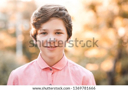 Smiling teen boy 14-15 year old wearing pink shirt posing over nature background. Looking at camera. Childhood.