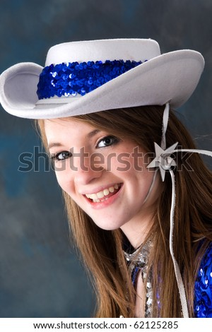 stock photo : Smiling teen cheerleader wearing white and blue hat.