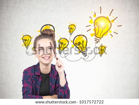 Smiling teen girl in a checkered shirt is sitting with a pencil near her forehead and thinking. She is looking up. A few yellow light bulbs drawn on a concrete wall #1017572722